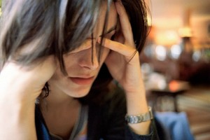 Woman holding her head, looking stressed.