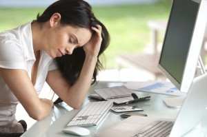 Financial Setbacks: Woman looking stressed at her desk, eyes closed