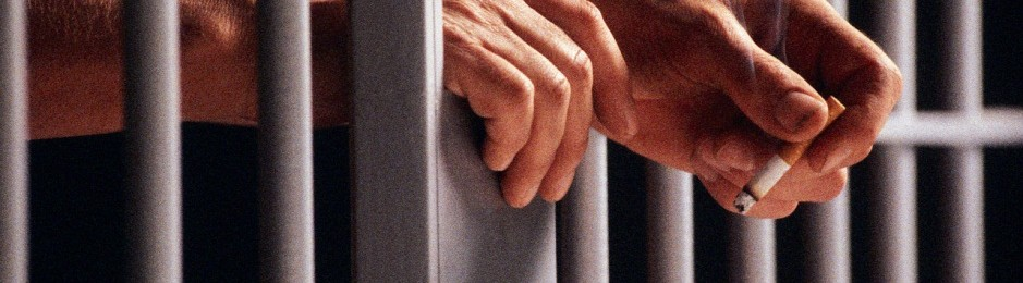 correctional counseling: man's hands with a cigarette through prison bars